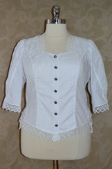 White cotton blouse with tone on tone embroidery details, lace trim on sleeve, neckline and hem.