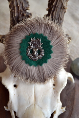 Round hat pin with badger hair wreath and cast metal deer motif at centre.
