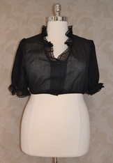 V-neck plus size dirndl blouse in black cotton with semi-sheer sleeves and ruffle around neckline.
